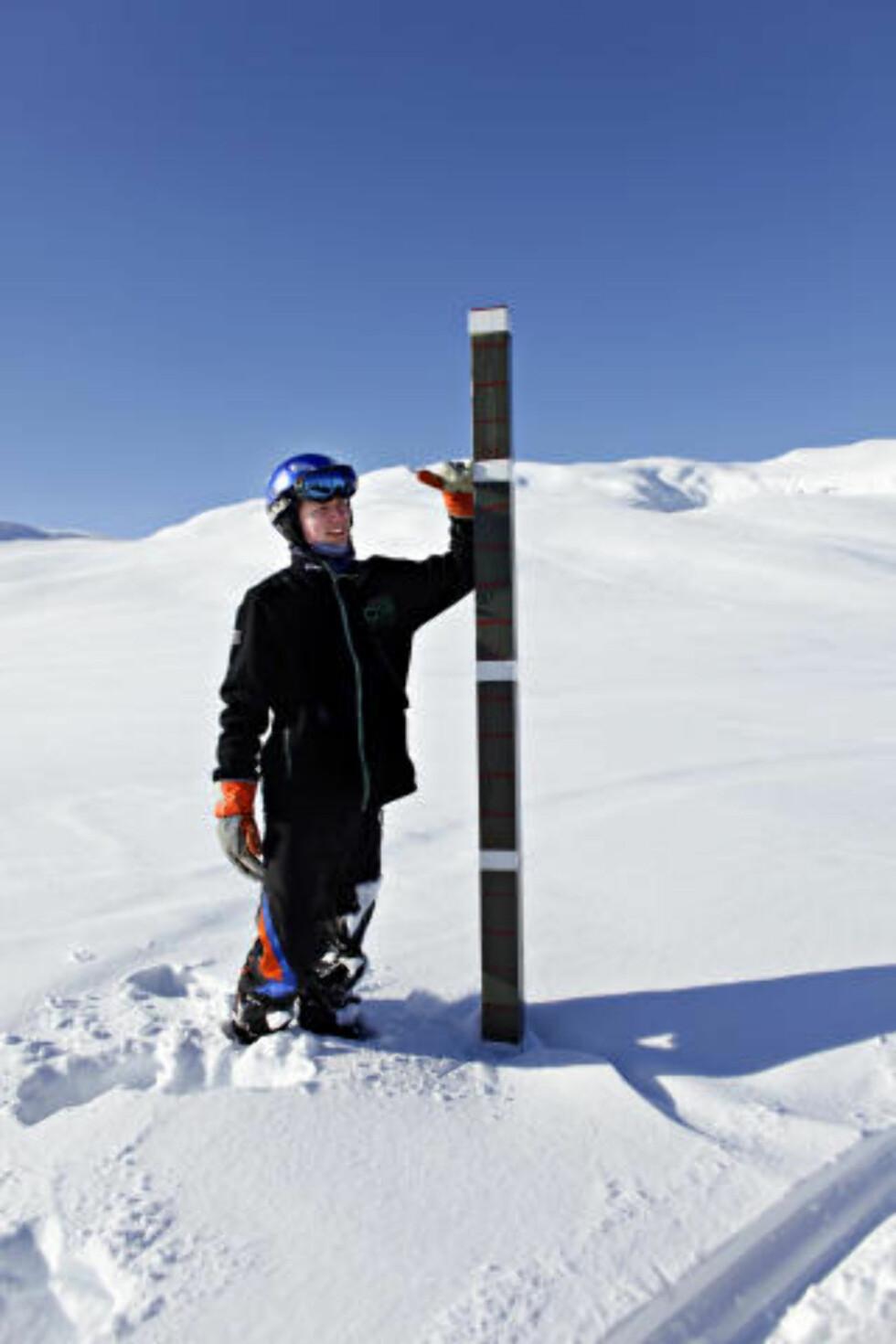 SNØDYBDEN: Jostein Norheim (16) viser hvor mye dypere snøen er på toppen av Kari Traa trekket. Voss Fjellandsby Myrkdalen, ledet snødybdestatistikken i februar. FOTO: Ole C. H. Thomassen