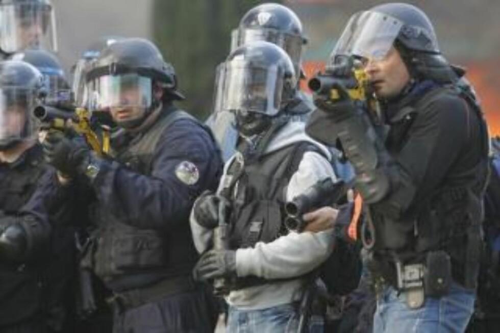 <strong>SIKTER:</strong> Politiet bruker tåregass og sjokkgranater for å spre menneskemengdene. (AP Photo/Christophe Ena)