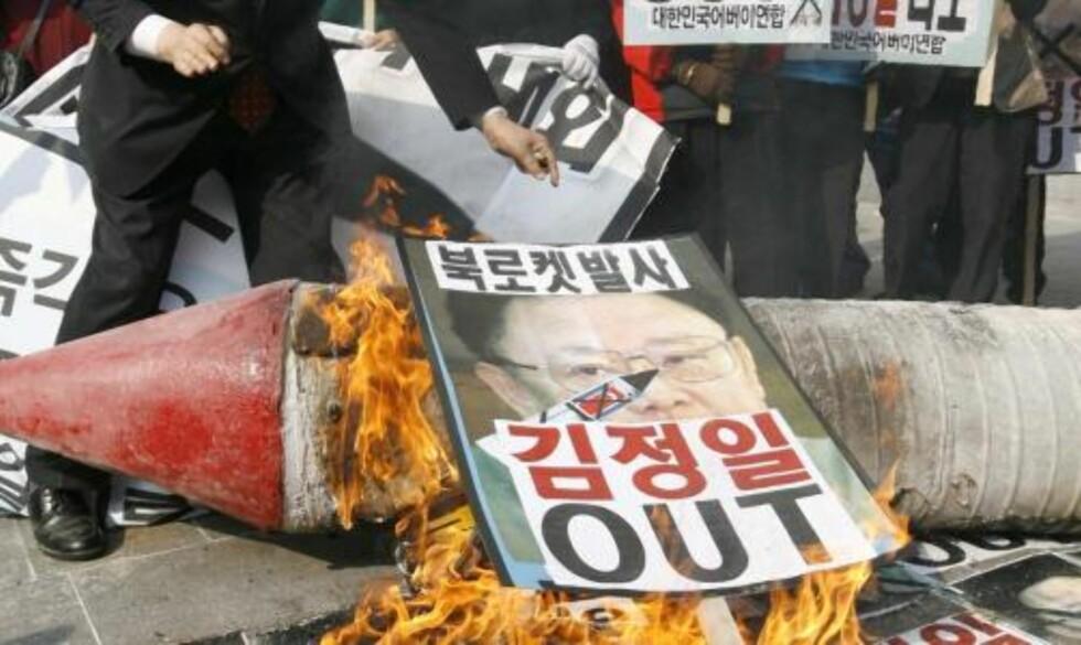 STERKE REAKSJONER: I Sør-Korea reagerte demonstranter i dag ved å brenne bilder av Nord-Koreas diktator Kim Jong Il. Foto: Scanpix