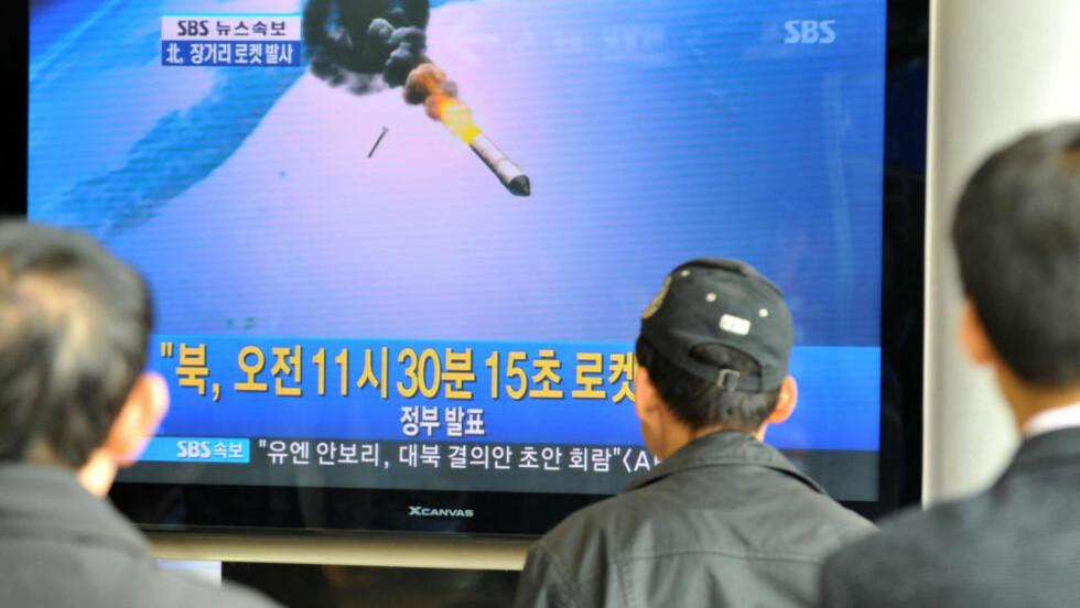 TRUER NABOSTATER: Sørkoreanere ser på en spesialsending om den nordkoreanske rakettoppskytingen i natt. Foto: AFP PHOTO/KIM JAE-HWAN/Scanpix