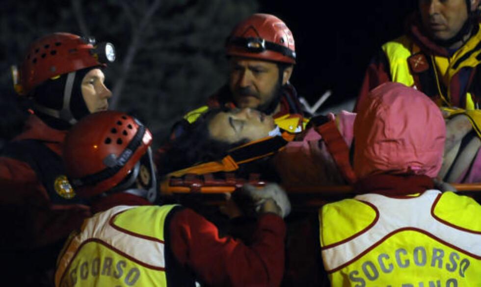 REDDET UT: En kvinne bæres ut av ruinene i live. 100 personer er reddet i løpet av natten. Foto: GIULIO PISCITELLI/AFP/SCANPIX