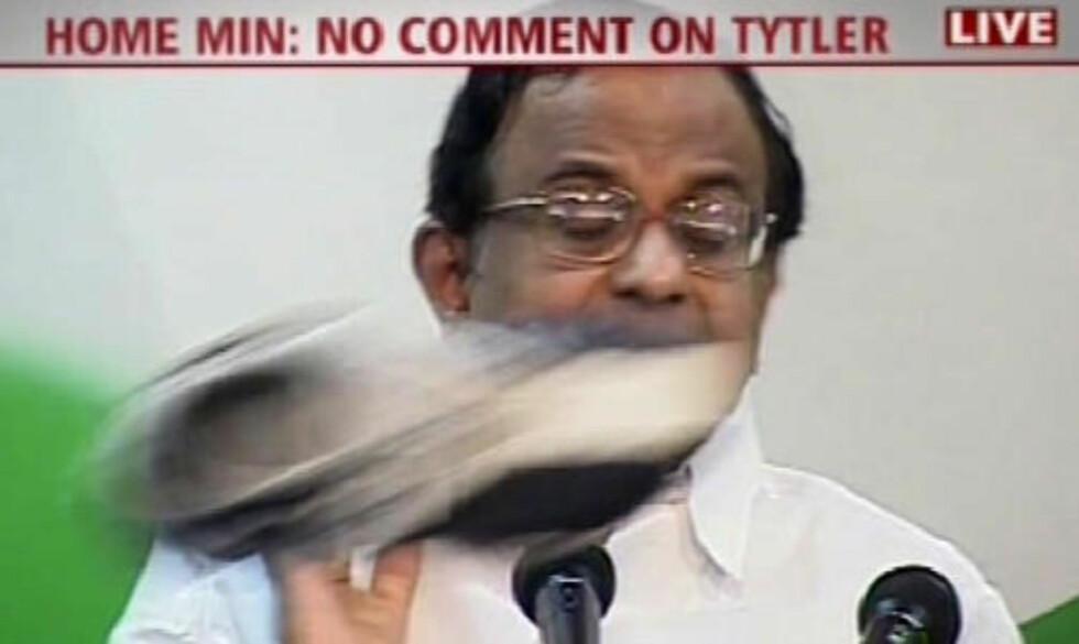 NY SKO Innenriksminister i India P.Chidambaram står på talerstolen når en sko farer forbi. En av journalistene i salen har åpenbart fått nok. Foto:  AFP PHOTO/CNN-IBN/SCANPIX