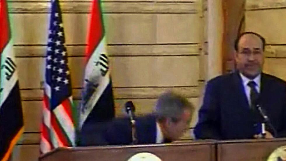 14. DESEMBER 2008: President George W. Bush dukker i det skoene til Muntazer al-Zaidi suser forbi under en pressekonferanse i Bagdad. Siden har journalisten sittet fengslet. Nå er straffen redusert fra tre til ett år i fengsel. Foto: AFP/DSK/SCANPIX