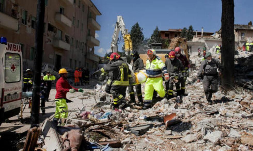 FRAKTET UT: Enda et lik fraktes ut av ruinene i byen L´Aquila i går. Foto: ESPEN RØST/Dagbladet