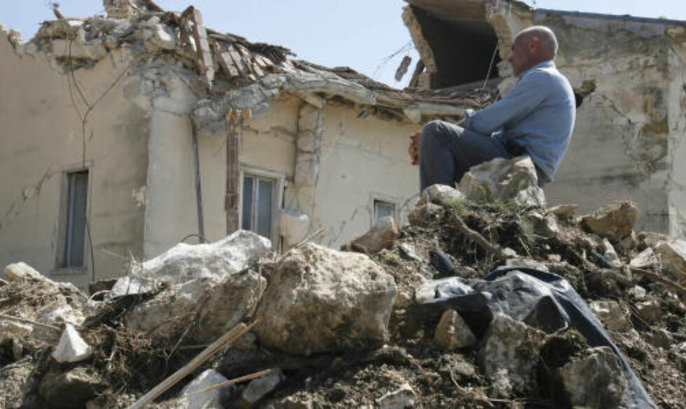 BARE RUINER IGJEN: En mann sitter på ruinene til det som en gang var et hjem i landsbyen Onna. Foto: AP/SCANPIX