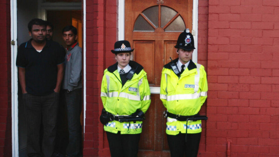 ANTITERRORAKSJON: Politibetjenter vokter inngangspartiet til en bolig som ble raidet i går. Naboene fulgte i går med på hasteaksjonen. Foto: AP Photo/Martin Rickett/Scanpix