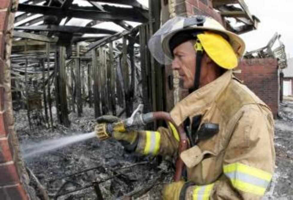 TUNG JOBB: Brannmann Bill Lott prøver å redde restene av et nedbrent hus. Foto: EPA/Bill Waugh/Scanpix