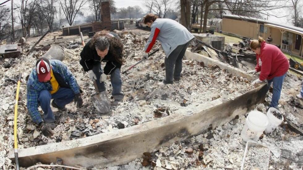 STORE SKADER: Rene Holbrook og LaRay Brown (i midten) får hjelp av venner til å se etter uskadde eiendeler etter at huset deres har brent ned til grunnen i Midwest City i Oklahoma. Brannen er trolig påsatt. Foto: EPA/Bill Waugh/Scanpix