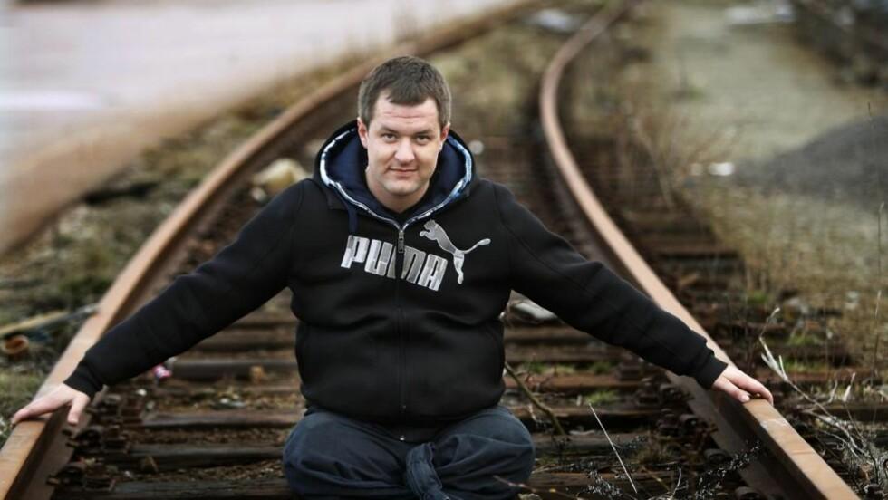 ELSKER TOG: - Back on track, sier Tom, mens han sitter på togskinnene. Han er ikke redd. Faktisk så elsker han å kjøre tog. Foto: Erling Hægeland