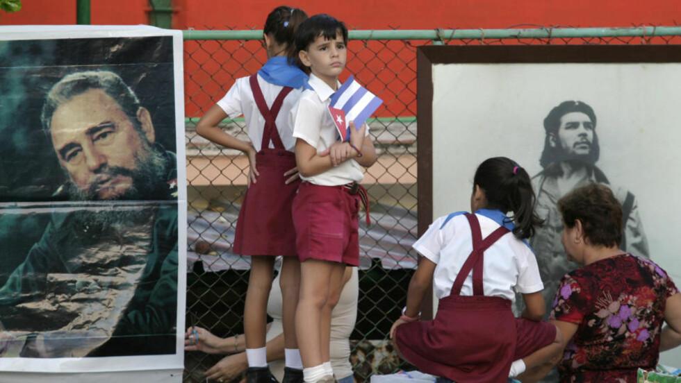 MER KONTAKT: Skolebarn i Cubas hovedstad Havana foran bilder av revolusjonsheltene Fidel Castro og Che Guevara. Nå har Det hvite hus uttalt at de lemper på reiserestriksjoner og pengeoverføringer mellom de to landene. Foto: Enrique De La Osa/Reuters/Scanpix