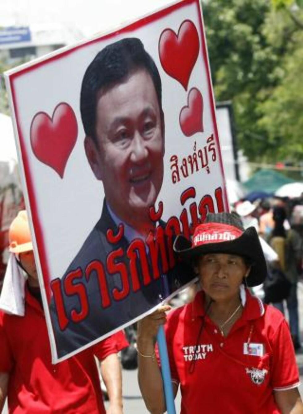 MANGE STØTTESPILLERE: Tilhengere av Thailands eksstatsminister Thaksin Shinawatra bærer med seg et bilde av det styrtede regjeringssjefen etter å ha avsluttet en okkupasjon i regjeringsområdet i Bangkok i dag. Foto: REUTERS/SCANPIX