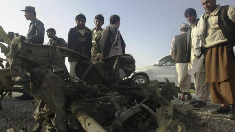 TOTALVRAK: Lokale afghanske innbyggere ser på vraket av bilen som ble ødelagt i eksplosjonen, der en norsk stabsoffiser i e-tjenesten ble drept.  Foto: AP Photo/Eltaf Najafizada/SCANPIX