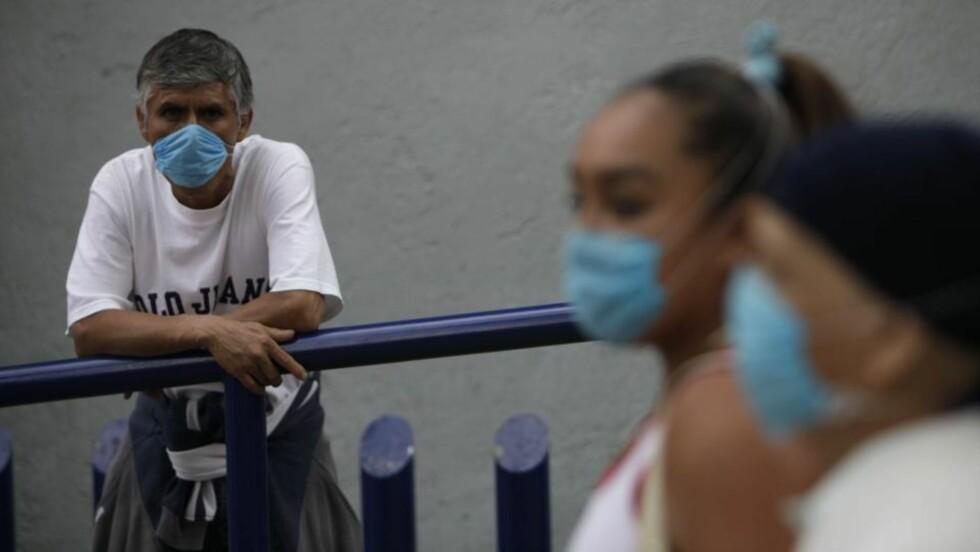 BESKYTTER SEG: Folk bruker munnbind og plasthansker for å unngå smitten. Foto: Gregory Bull/AP/Scanpix