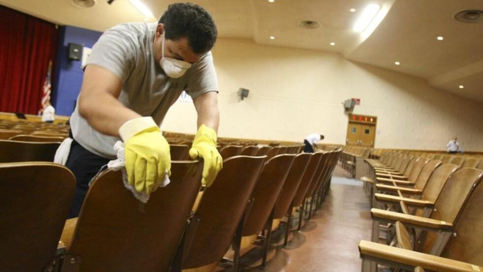 SKRUBBER: Ikledd ansiktsmasker rengjør personalet St. Francis Preparatory School i Queens, New York. Flere tillfeller av svineinfluensa er bekreftet hos elever, etter en tur til Mexico hvor sykdommen først hadde utbrudd. Foto: EPA/SCANPIX