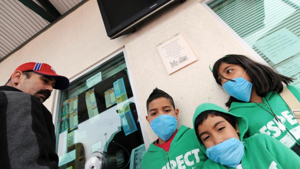 SMITTEFRYKT: Meksikanske barn står ved grensen mellom California og Mexico. Foto: SCANPIX/AFP PHOTO/Jewel SAMAD