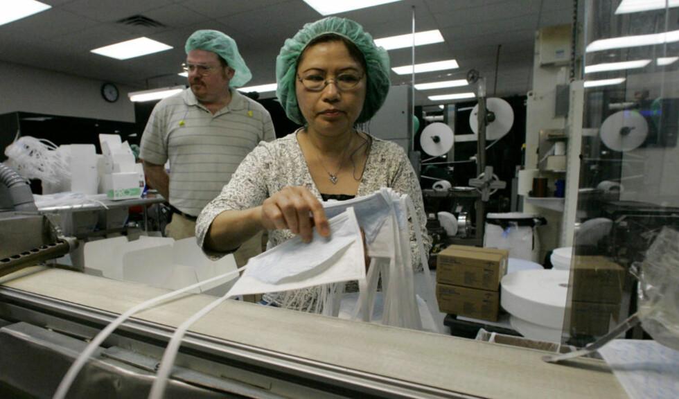 TOÅRING BEKREFTET DØD:  Svineinfluensaen har nå krevd sitt første liv utenfor Mexico. På denne fabrikken i Texas, staten der toåringen bodde, jobbes det på spreng for å produsere munnbind. Foto: Scanpix