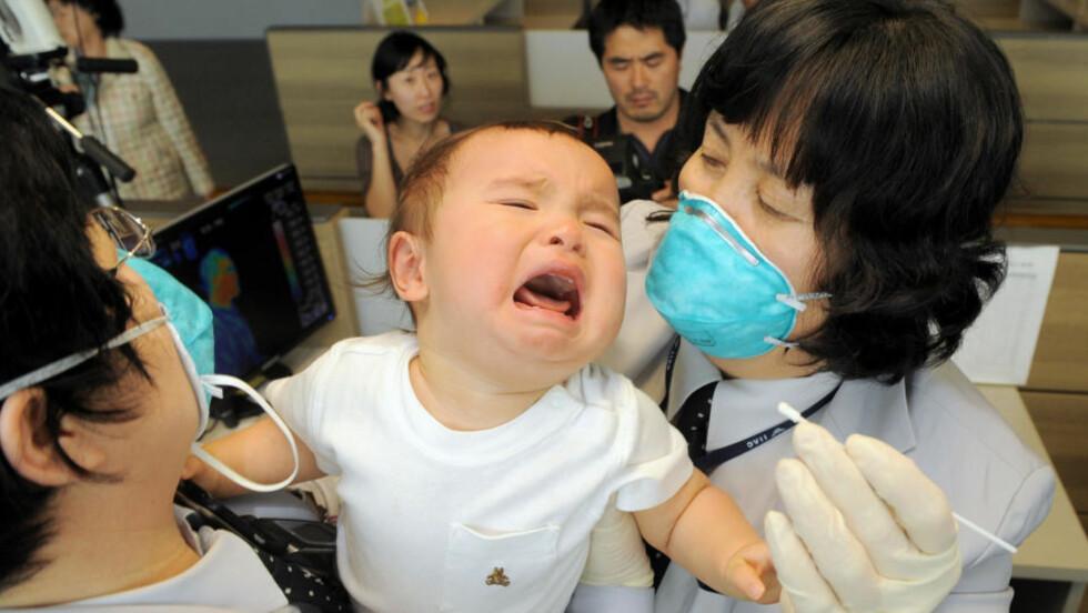 SVINEINFLUENSAFRYKT: Sør-Koreanske myndigheter tar prøver av en baby som ankom Icheon flyplass fra USA. Foto: SCANPIX/AFP PHOTO/POOL/JUNG YEON-JE