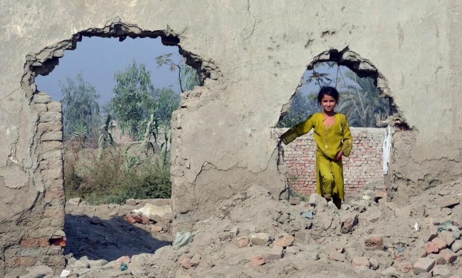 FLYKTNING: En ung afghansk flyktning i restene av et hus i en flyktningleir i utkanten av Peshawar. Mer enn 350 000 afghanske flyktninger har returnert til hjemlandet fra Pakistan, viser nye tall fra FN. Foto: AFP / NTB Scanpix