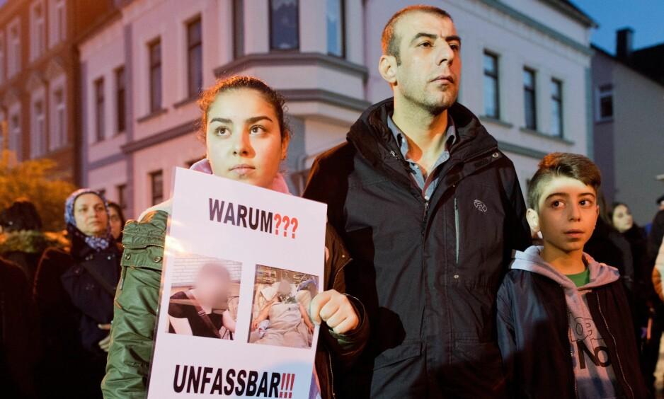 """SJOKKERT: Offerets bror og hans to barn holder opp plakater med påskriften """"Hvorfor??"""" og """"Utrolig"""". FOTO: EPA/JULIAN STRATENSCHULTE/ NTB Scanpix."""