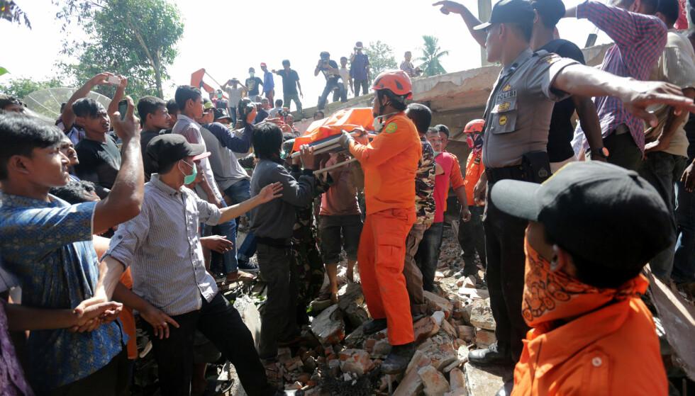 MANGE DØDE: Redningsarbeidere henter et offer ut av en bygning som kollapset i jordskjelvet utenfor byen Lueng Putu, i den nordlige Aceh-provinsen i Indonesia. Det er så langt meldt om minst 54 døde. Foto. Antara Foto/ Irwansyah Putra