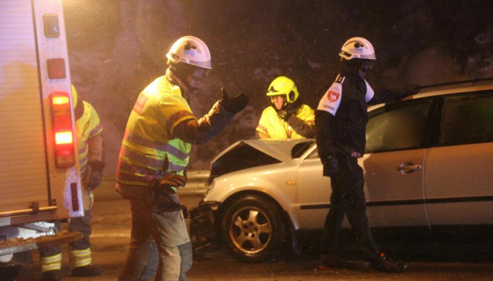 KREVENDE FORHOLD: Brannvesenet måtte bruke sine egne biler som skjold mot vinden, da de jobbet med å redde ut tre personer etter en trafikkulykke i Hammerfest torsdag kveld. Foto: Thomas Patrick Christensen