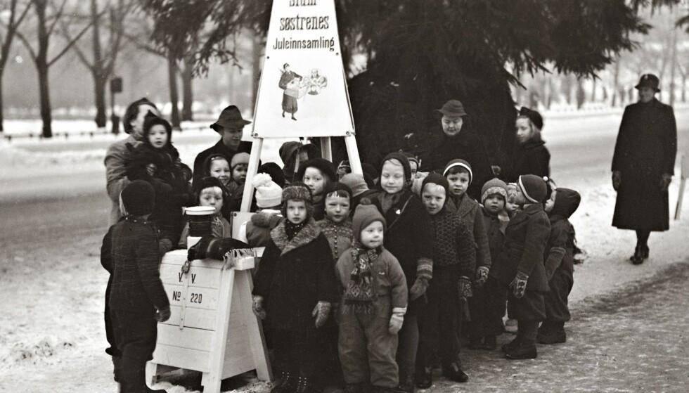 HOS SLUMSØSTRENE: Oslo, desember 1940. Slumsøstrenes juleinnsamling ved julegranen på Universitetsplassen på Karl Johan. Barnehagebarn besøker innsamlingen.