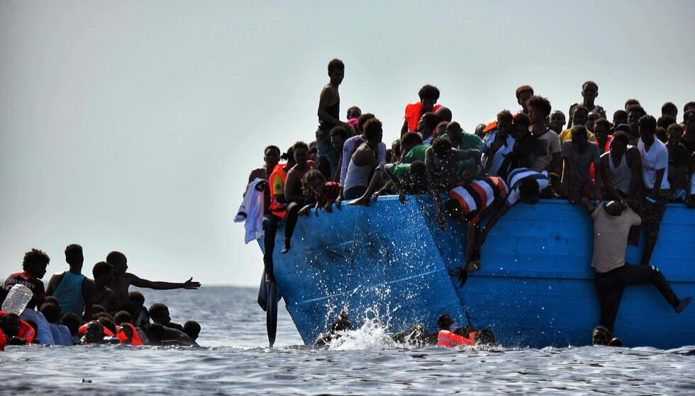 RISIKERER LIVET: Migranter klamrer seg fast til båtripa 12 nautiske mil fra kysten av Libya i oktober i år. Antallet som legger ut på havet mellom Libya og Italia har gått opp fra ca. 154,000 mennesker i fjor til ca. 175,000 i år. Foto: AFP PHOTO / ARIS MESSINIS