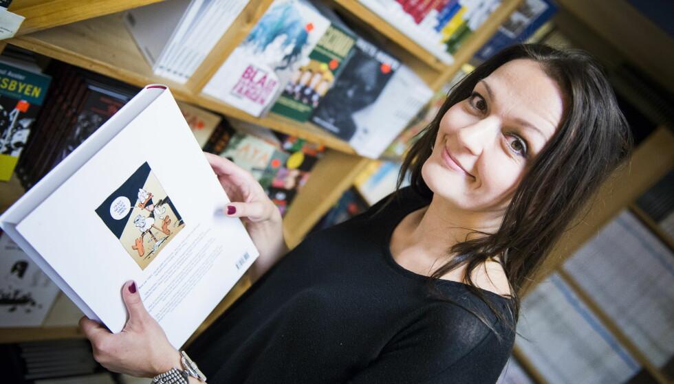 """20 år: Lise Myhre har figurert med Nemi på den norske tegneseriehimmelen i snart 20 år. 5.000 striper om den svartkledde heltinnen har det blitt. Her på tegneserieforretningen Tronsmo i Oslo, med hennes største inspirator Charlie Christensens """"Arne And"""". Foto: Endre Vellene"""