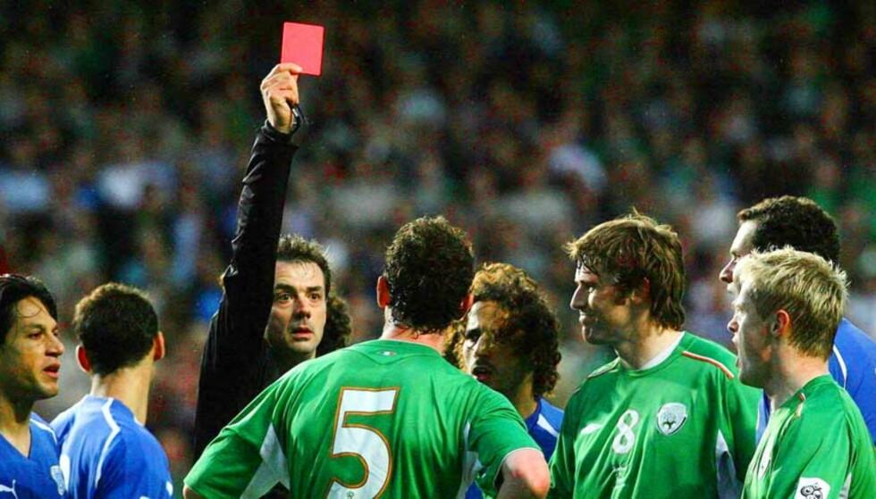 ET VANLIG RØDT KORT: Det er spillerne som skal utvises, ikke linjemannen. Her får irske Andy O\'Brien marsjordre av dommer Kyros Vassaras. Foto: SCANPIX/AP