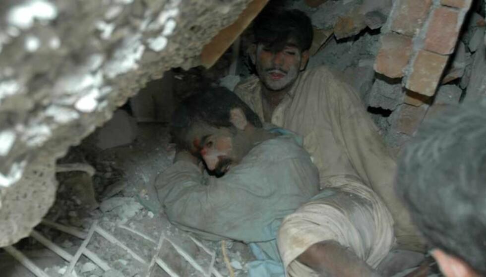 REDDET: Seint i går kveld kom det fortsatt fortvilte skrik inne fra ruinhaugen av det som var en ti etasjers leilighetsblokk fem mil utenfor i Islamabad i Pakistan. Mennene på bildet ble reddet fra ruinhaugen. Alle foto: B. K. Bangash/Ap/Scanpix