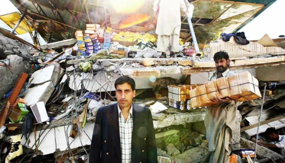 FARSARVEN: Mahmood Zarif står i ruinene av det som var «Kashmir Boot House», hvor de ansatte prøver å samle sammen skoeskene på et golv som liksom henger i lufta. Foto: Sveinung Uddu Ystad