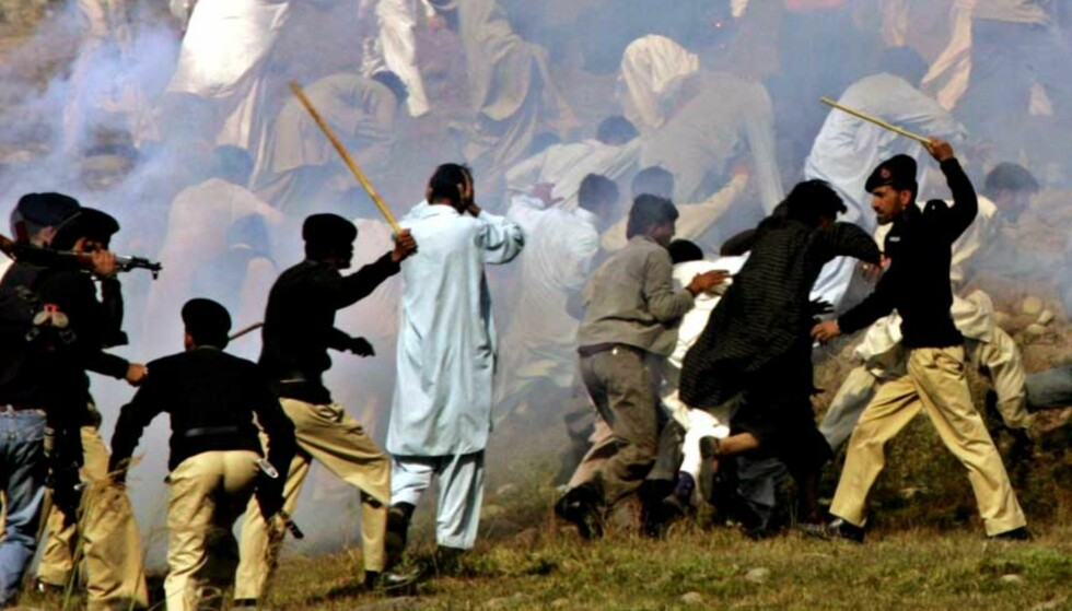 MED KJEPPER:  Politi og sivile kasjmirere sloss da Pakistan og India åpnet Kontrollinja som deler Kashmir. Foto: Scanpix