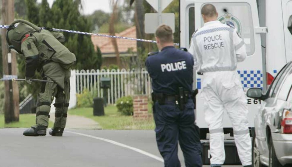 STOR AKSJON: En politimann i verneutstyr undersøker mistenkelige pakker og kjøretøy. 17 menn ble pågrepet i en storstilt antiterroraksjon i Australia i går. Foto: Mark Baker/AP/Scanpix