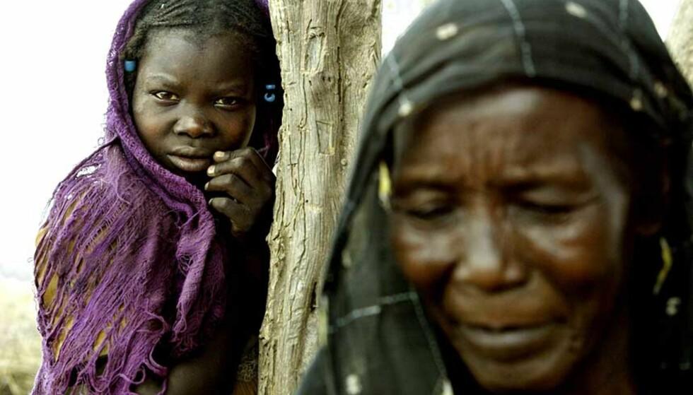 KATASTROFE:  Da Dagbladet besøkte Darfur-provinsen i Sudan i 2004 fortalte folk om massedrap, voldtekter og nedbrenning av hele landsbyer. Noura Adam mister begge foreldrene da den regjeringsstøttede janjaweedmilitsen angrep landsbyen deres. Hun har bare bestemora Hawo Ahmad Hassan igjen. Mens fredsforhandlingene om Darfur stadig utsettes dør menneskene det handler om. Foto: TORE BERGSAKER