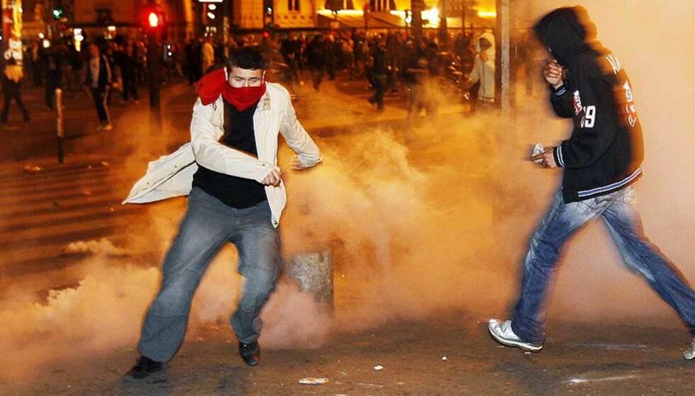 GJENNOM TÅREGASSEN: Demonstranter prøver å unnslippe tåregassen som opprørspolitiet brukte mot opptøyene på Place de la Bastille. Foto: ERIC GAILLARD/REUTERS/SCANPIX