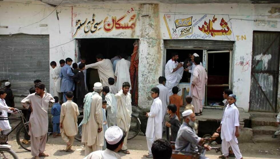BOMBE: Folk samler seg utenfor platebutikkene Muskan CD-senter og Shabana CD-hus etter en bombe har blitt sprengt i Charssada, 28 kilometer fra Peshawar, Pakistan. Foto: Scanpix/AP