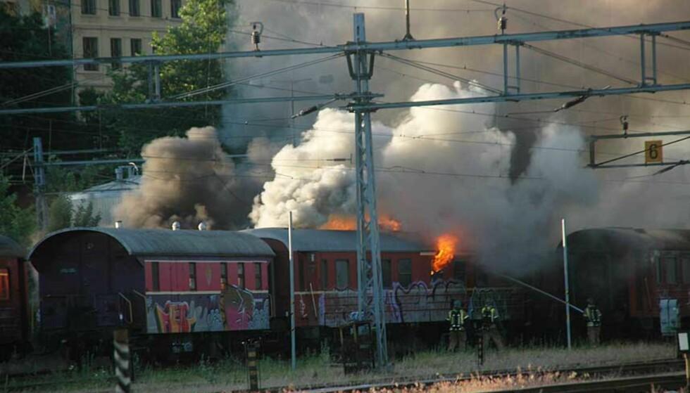 SLUKKER NÅ: Brannvesenet har fått kontroll på mesteparten av flammene, etter at disse togsettene sto i full fyr tidligere onsdag morgen. Foto: Hilde Marie Tvedten
