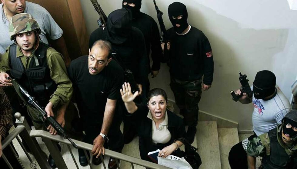 STORMET PARLAMENTSBYGNINGEN: Parlamentsmedlem Jihad Abu Znaid fra Fatah, med hånden opp, reagerer på at militante fra al-Aqza-martyrenes brigade, tilknyttet Fatah, stormer den palestinske parlamentsbygningen i byen Ramallah på Vestbredden. Foto: Muhammed Muheisen/AP/Scanpix