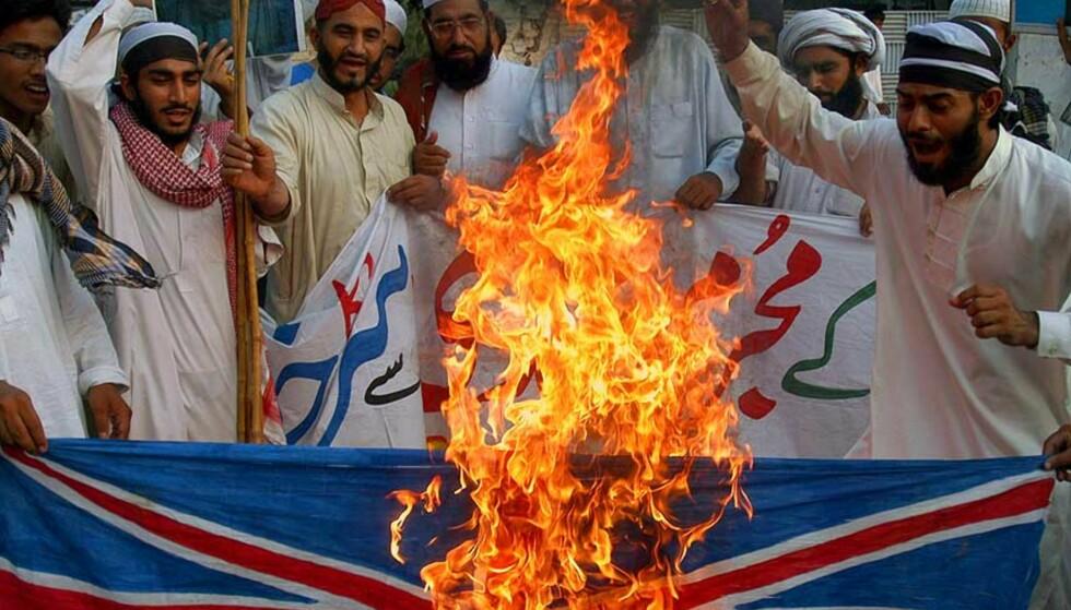 LAHORE; PAKISTAN:  Pakistanske muslimer brenner et britisk flagg i protest mot adlingen av Salman Rushdie. Foto: AFP PHOTO/ Scanpix, Arif ALI