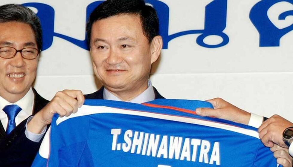 FOTBALLGAL: Her poserer den tidligere statsministeren Thaksin Shinawatra med en Manchester City-trøye i regjeringsbygget i Bangkok i 2004. To år senere ble han kuppet etter beskyldninger om korrupsjon. Nå kan han bli ny eier av den engelske fotballklubben. Foto: AP