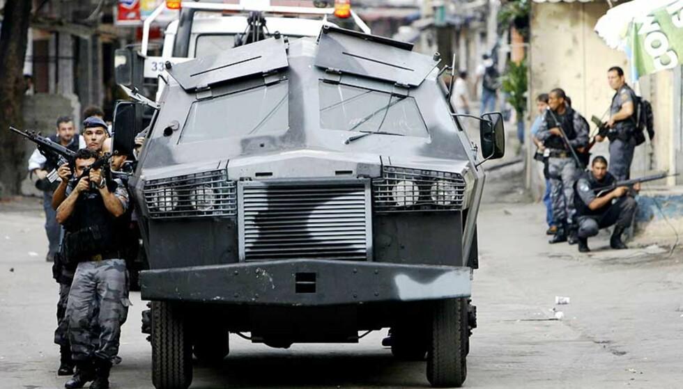 RYKKER FRAM: Tungt bevæpnede politifolk rykker inn i bydelen Alemao. Foto: RICARDO MORAES/AP/SCANPIX