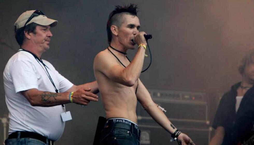 IKKE AKKURAT SKANDALE:  Vokalist i Flying Crap Rune Tengs, satt en tom sprøyte i armen på seg selv på scenen under Hovefestivalen i dag. Men først gjorde han det klart at bandet var imot narkotika. Foto: Eirik Helland Urke