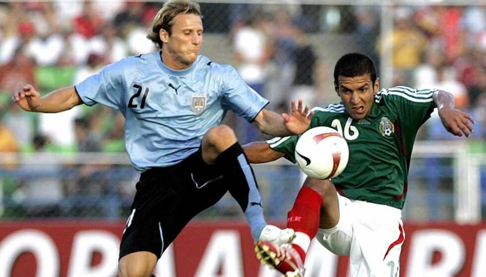 TØFFE TAK: Mexicos Jaime Lozano (t.h.) kaster seg inn i en duell med Uruguays Diego Forlan. Til slutt var det førstnevnte som kunne juble for bronse i Copa America. Foto: CHICO SANCHEZ/EPA/SCANPIX