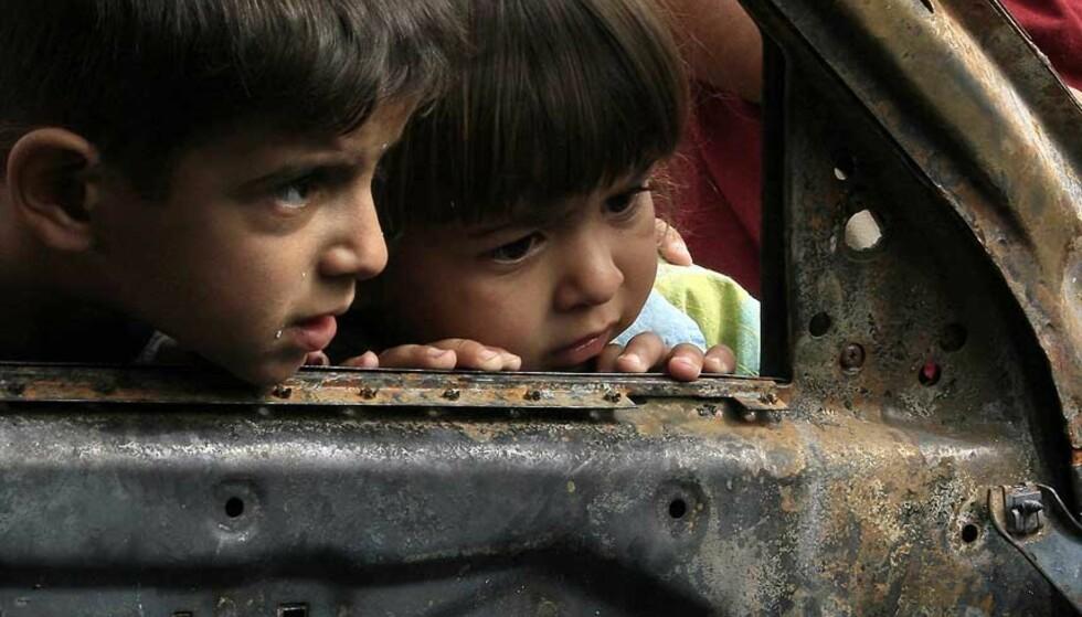 UTBRENT BIL: To barn undersøker restene av et utbrent bilvrak, i Sadr City i Bagdad. To mennesker ble drept og fire såret, under et nattlig angrep her, 10. juli. Foto: SCANPIX/AFP/WISSAM AL-OKAILI