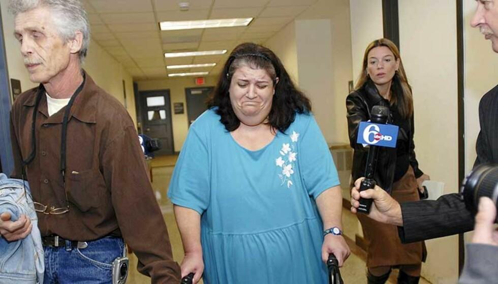 GRÅTKVALT: Michele Cossey ble pågrepet under sønnens høring i dag. Her følges hun til rettsalen av sin mann, Frank. Michele er siktet for å ha kjøpt våpen til sin sønn. Foto: AP PHOTO/SCANPIX