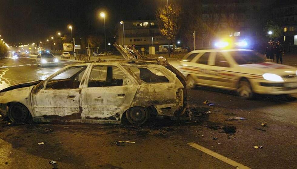 <strong><b>BILER I BRANN:</strong></b> En politibil patruljerer i gatene, like ved vraket av en utbrent bil. Flere politistasjoner ble angrepet, etter at to gutter døde i en kollisjon med en politibil, i Villiers-le-Bel, nord for Paris. Foto: SCANPIX/REUTERS/Gonzalo Fuentes