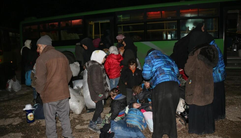 FLYKTER: Her står mennesker klare til å flykte fra Øst-Aleppo til Idlib-provinsen. Både busser og ambulanser tas i bruk i evakueringen. Mahmoud Faisal / Anadolu Agency / NTB Scanpix