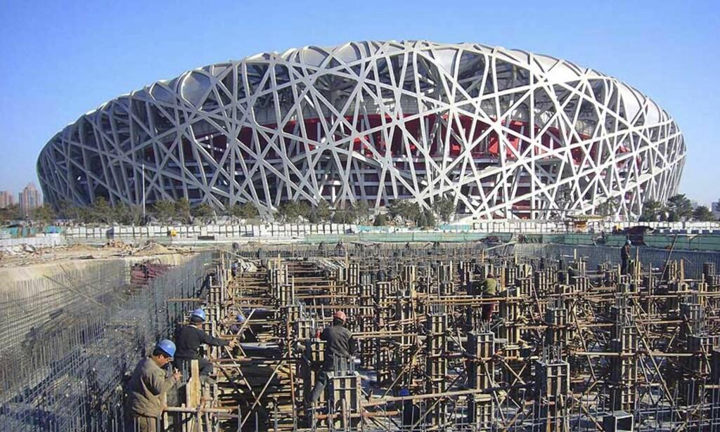 KONTROVERS: Arbeidet med det såkalte Fugleredet, som er en gigantisk sportsarena i Kinas hovedstad Beijing, fortsetter. Men kinesiske myndigheter benekter at minst ti arbeidere har mistet livet under byggingen av OL-arenaen. Foto: REUTERS/China Daily/SCANPIX