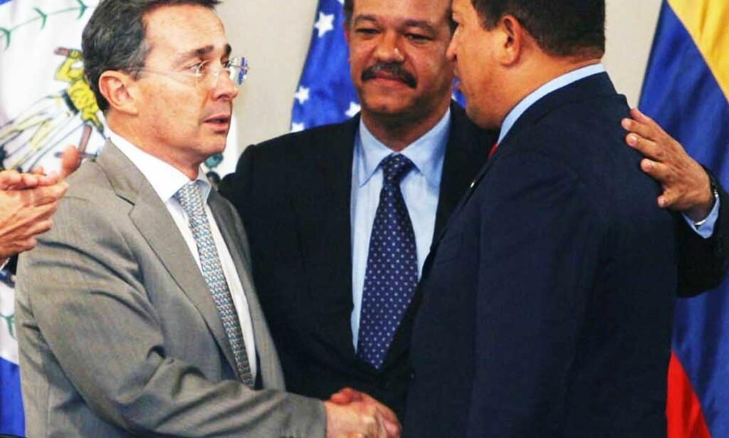 «VENNER» IGJEN: En noe motvillig Alvaro Uribe, Colombias president (t.v.), tar Venezuelas president Hugo Chávez (t.h.) i hånda på oppfordring fra Leonel Fernández, president for Den dominikanske republikk og vert for toppmøtet i Rio-gruppa. Foto: MIRAFLORES/AFP/SCANPIX