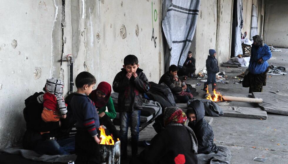 KRIG: Evakuerte barnefamilier prøver å holde varmen over et bål. I dag ble rundt 5000 personer fra Øst-Aleppo evakuert. Foto: Sipausa / NTB Scanpix